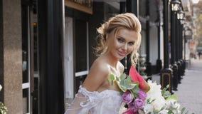 Πορτρέτο μιας όμορφης νύφης με μια ανθοδέσμη στην πόλη φιλμ μικρού μήκους