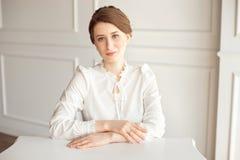 Πορτρέτο μιας όμορφης χαμογελώντας νέας επιχειρηματία brunette σε μια άσπρη συνεδρίαση πουκάμισων σε έναν φωτεινό σύγχρονο τερματ στοκ φωτογραφίες με δικαίωμα ελεύθερης χρήσης