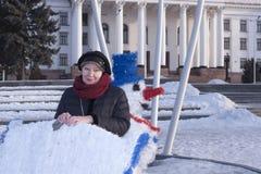 Πορτρέτο μιας ώριμης γυναίκας που στέκεται κοντά στους αποτυπωμένους χειμερινούς χαρακτήρες στο τετράγωνο στοκ εικόνα με δικαίωμα ελεύθερης χρήσης