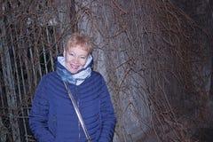 Πορτρέτο μιας ώριμης γυναίκας που στέκεται μπροστά από έναν φράκτη που στρίβεται από τις μη ανθισμένες εγκαταστάσεις στοκ εικόνα