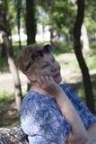 Πορτρέτο μιας ώριμης συνεδρίασης γυναικών σε ένα πάρκο σε έναν πάγκο στοκ φωτογραφία