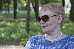 Πορτρέτο μιας ώριμης συνεδρίασης γυναικών σε ένα πάρκο σε έναν πάγκο στοκ φωτογραφίες