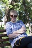 Πορτρέτο μιας ώριμης συνεδρίασης γυναικών σε ένα πάρκο σε έναν πάγκο στοκ εικόνες