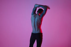 Πορτρέτο μόδας στούντιο του προκλητικού φίλαθλου ατόμου Μυϊκός γυμνός κορμός από πίσω σε ένα ρόδινο υπόβαθρο Στοκ Φωτογραφία