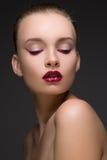 Πορτρέτο μόδας της τέλειας γυναίκας με τα κόκκινα ή καφέ χείλια και ροδανιλίνης κατώτατο σημείο βελών των ματιών στο σκούρο γκρι  στοκ φωτογραφία