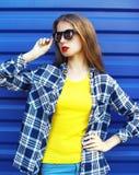 Πορτρέτο μόδας του αρκετά μοντέρνου κοριτσιού στα γυαλιά ηλίου και τα ζωηρόχρωμα ενδύματα πέρα από το μπλε Στοκ φωτογραφία με δικαίωμα ελεύθερης χρήσης