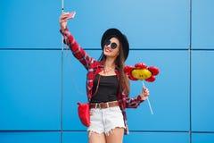 Πορτρέτο μόδας του αρκετά χαμόγελου και της γυναίκας στα γυαλιά ηλίου με το smartphone ενάντια στο ζωηρόχρωμο μπλε τοίχο Κάνετε s Στοκ φωτογραφία με δικαίωμα ελεύθερης χρήσης