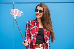 Πορτρέτο μόδας χαμογελώντας της αρκετά hipster γυναίκας στο smartphone γυαλιών ηλίου ενάντια στο ζωηρόχρωμο μπλε τοίχο Παραγωγή s Στοκ Φωτογραφίες