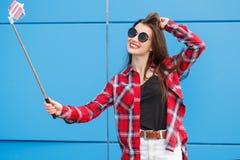 Πορτρέτο μόδας χαμογελώντας της αρκετά hipster γυναίκας στο smartphone γυαλιών ηλίου ενάντια στο ζωηρόχρωμο μπλε τοίχο Παραγωγή s Στοκ Εικόνες