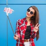 Πορτρέτο μόδας χαμογελώντας της αρκετά hipster γυναίκας στο smartphone γυαλιών ηλίου ενάντια στο ζωηρόχρωμο μπλε τοίχο Παραγωγή s Στοκ Εικόνα
