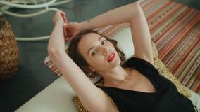 Πορτρέτο νέο όμορφο να βρεθεί γυναικών brunette στον καναπέ και του χαμόγελου σε μια κάμερα στοκ εικόνες