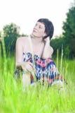 Πορτρέτο να ονειρευτεί και της χαλάρωσης της καυκάσιας τοποθέτησης γυναικών Brunette υπαίθρια στο υπόβαθρο φύσης στο ηλιοβασίλεμα Στοκ Εικόνες