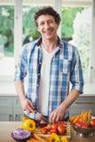 Πορτρέτο να χαμογελάσει τα τέμνοντα λαχανικά ατόμων στο σπίτι Στοκ Εικόνες