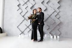 Πορτρέτο νυφών και νεόνυμφων στο στούντιο Απομονωμένος στο γκρίζο γεωμετρικό υπόβαθρο Ξηρός καπνός πάγου στο πάτωμα Στοκ φωτογραφία με δικαίωμα ελεύθερης χρήσης