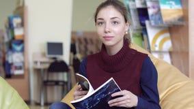 Πορτρέτο ξεφυλλίσματος γυναικών σπουδαστών χαμόγελου του ρομαντικού μέσω ενός βιβλίου στο δωμάτιο ανάγνωσης φιλμ μικρού μήκους