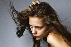 Πορτρέτο ομορφιάς κινηματογραφήσεων σε πρώτο πλάνο ενός προκλητικού κοριτσιού brunette με την πετώντας τρίχα Στοκ Εικόνα