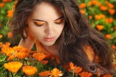 Πορτρέτο ομορφιάς. Μάτι Makeup. Το κορίτσι ομορφιάς πέρα από marigold ανθίζει το φ Στοκ Φωτογραφία