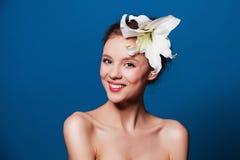 Πορτρέτο ομορφιάς της ευτυχούς γυναίκας με το λουλούδι κρίνων στο μπλε Στοκ φωτογραφία με δικαίωμα ελεύθερης χρήσης