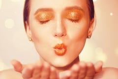 Πορτρέτο ομορφιάς του νέου κομψού κοριτσιού Όμορφη γυναίκα brunette με τα χρυσά χείλια και το χρυσό φωτεινό makeup, φύσηγμα καρφι Στοκ εικόνες με δικαίωμα ελεύθερης χρήσης