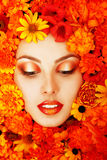 Πορτρέτο ομορφιάς του όμορφου θηλυκού προσώπου με τα πορτοκαλιά λουλούδια Στοκ εικόνες με δικαίωμα ελεύθερης χρήσης