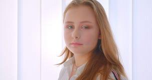 Πορτρέτο πλάγιας όψης κινηματογραφήσεων σε πρώτο πλάνο της νέας αρκετά καυκάσιας στροφής κοριτσιών και της εξέτασης τη κάμερα στο απόθεμα βίντεο