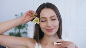 Πορτρέτο που βλασταίνεται της χαμογελώντας όμορφης γυναίκας με το λουλούδι στην τρίχα απόθεμα βίντεο