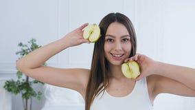 Πορτρέτο που βλασταίνεται της όμορφης νέας τοποθέτησης γυναικών με δύο μισό του μήλου απόθεμα βίντεο