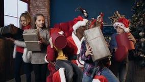 Πορτρέτο που βλασταίνεται των μικρών παιδιών που τα δώρα που παίρνουν από Άγιο Βασίλη στο υπόβαθρο χριστουγεννιάτικων δέντρων απόθεμα βίντεο