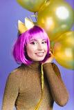 Πορτρέτο που γοητεύει τη νέα γυναίκα με τα χρυσά μπαλόνια που γιορτάζει το νέο κόμμα έτους, καρναβάλι στο ιώδες υπόβαθρο Πορφύρα  στοκ εικόνες με δικαίωμα ελεύθερης χρήσης