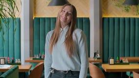 Πορτρέτο που πυροβολείται της ελκυστικής γυναίκας που εξετάζει τη κάμερα και που χαμογελά εργαζόμενης στο αστικό γραφείο o απόθεμα βίντεο