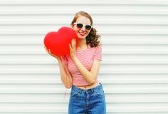 Πορτρέτο που χαμογελά τη νέα γυναίκα με τη μορφή καρδιών μπαλονιών αέρα που έχει τη διασκέδαση πέρα από το λευκό Στοκ Εικόνες