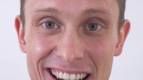 Πορτρέτο προσώπου περικοπών του ευτυχούς ελκυστικού νεαρού άνδρα που εξετάζει τη κάμερα και το χαμόγελο που απομονώνονται στο άσπ φιλμ μικρού μήκους