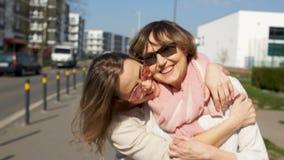 Πορτρέτο πόλεων της μητέρας και της κόρης Δύο γυναίκες αγκαλιάζουν και γελούν χαρούμενα Θερινό πορτρέτο απόθεμα βίντεο
