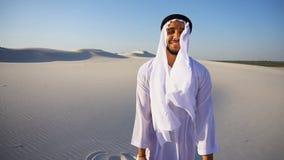 Πορτρέτο σε αργή κίνηση βέβαιο αρσενικό αραβικό Sheikh Ε.Α.Ε. σε Kandura στη μέση της άσπρης ερήμου τη σαφή ημέρα φιλμ μικρού μήκους