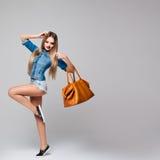 Πορτρέτο στούντιο ενός μοντέρνου τετραγωνικού φορέματος τζιν γυναικών με τα μακριά ξανθά μαλλιά, κόκκινα χείλια, μακριά πόδια, τσ Στοκ Εικόνες