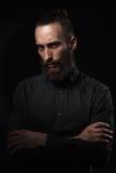 Πορτρέτο στούντιο ενός όμορφου ατόμου με μια γενειάδα στο μαύρο shir Στοκ Εικόνες