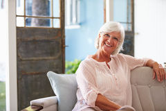 Πορτρέτο συνεδρίασης γυναικών χαμόγελου της ανώτερης στον καναπέ στο σπίτι στοκ εικόνα με δικαίωμα ελεύθερης χρήσης