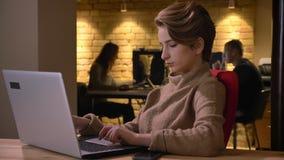 Πορτρέτο σχεδιαγράμματος της συγκεντρωμένης νέας με κοντά μαλλιά γυναίκας που δακτυλογραφεί προσεκτικά στο lap-top στην αρχή απόθεμα βίντεο