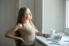 Πορτρέτο σχεδιαγράμματος μιας νέας γυναίκας, τεντώνοντας εργασία στο lap-top Στοκ Εικόνες
