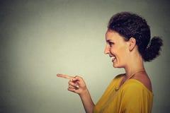 Πορτρέτο σχεδιαγράμματος πλάγιας όψης της ελκυστικής γυναίκας που δείχνει και που γελά σε κάποιο Στοκ Φωτογραφίες
