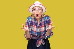 Πορτρέτο της έκπληκτης σύγχρονης μοντέρνης ώριμης γυναίκας στο περιστασιακό ύφος με το καπέλο και eyeglasses που στέκονται, αυξημ στοκ εικόνα με δικαίωμα ελεύθερης χρήσης