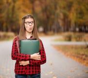 Ο νέος σπουδαστής με το έκπληκτο πρόσωπο κοιτάζει από το φάκελλο στο κόκκινο ελεγμένο πουκάμισο Πορτρέτο της έξυπνης νέας γυναίκα στοκ εικόνες