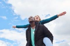 Πορτρέτο της αγάπης του νέου διεθνούς ζεύγους στο υπόβαθρο ουρανού Αφρικανικός τύπος και καυκάσια γυναίκα Στοκ φωτογραφία με δικαίωμα ελεύθερης χρήσης