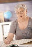 Ανώτερος δάσκαλος στο σχολείο που ψάχνει σε ένα βιβλίο Στοκ Φωτογραφία
