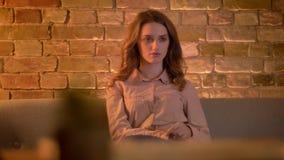 Πορτρέτο της απορροφημένης νέας συνεδρίασης έφηβη στον καναπέ και τη TV προσοχής στην άνετη εγχώρια ατμόσφαιρα απόθεμα βίντεο
