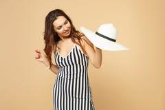 Πορτρέτο της αρκετά νέας γυναίκας στο γραπτό ριγωτό φόρεμα που κρατά υπό εξέταση, που κοιτάζει στο καπέλο στο μπεζ κρητιδογραφιών στοκ εικόνες με δικαίωμα ελεύθερης χρήσης