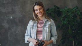 Πορτρέτο της αρκετά νέας ξανθής στάσης στο διαμέρισμα σοφιτών, του χαμόγελου ευτυχώς, της τοποθέτησης και της εξέτασης τη κάμερα  απόθεμα βίντεο