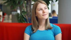 Πορτρέτο της αρκετά ονειροπόλου νέας γυναίκας στην μπλε συνεδρίαση μπλουζών στη σκέψη καφέδων Κόκκινο πράσινο δέντρο καναπέδων απόθεμα βίντεο