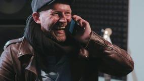 Πορτρέτο της αρσενικής ομιλίας μουσικών στο κινητό τηλέφωνο απόθεμα βίντεο