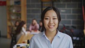Πορτρέτο της ασιατικής βέβαιας επιχειρηματία που εξετάζει τη κάμερα και που χαμογελά ενώ η πολυ-εθνική ομάδα της που εργάζεται στ απόθεμα βίντεο